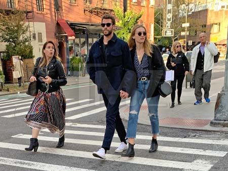 Liam Hemsworth and a mystery girl crossing the streets holding hands.