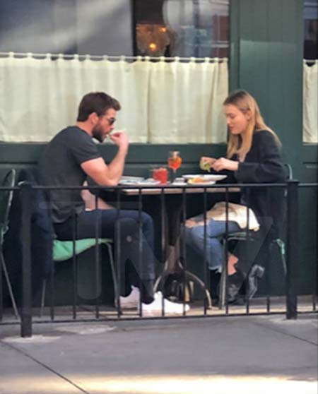 Liam and a girl sharing a meal while out.