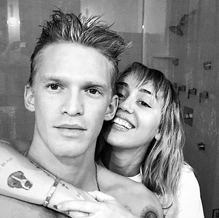 Cody Simpson and Miley Cyrus taking pictures in the bathroom.