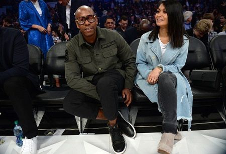 Dave and his wife sitting during a game at the NBA All-Star Game 2018 at Staples Center on February 18, 2018 in Los Angeles, California. In a dark green shirt is Dave with one of his arms under his lift thigh and Elaine is in a blue trenchcoat smiling with her hands cusped together over crossed legs.