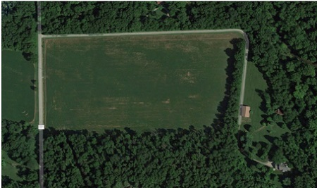 The aerial view of Dave Chappelle's empty green farm with his house seen very small from distance.