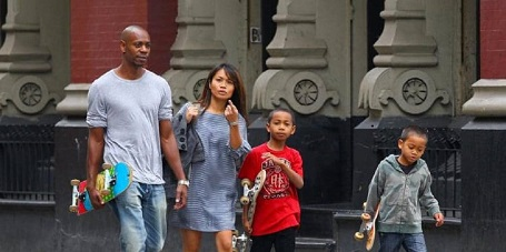 Dave Chappelle carrying a skateboard in his right hand, in blue jeans and grey T-shirt (Far left). Elaine raising her left hand with the index pointed at the camera as she looks shocked or furious at being photographed (second left). Sulayman carrying a skateboard in his right hand as he also has his left hand raised to his neck level in a red T-shirt (second right). Ibrahim looks indifferent to anything as he walks in a patterned hoodie with a skateboard in his right hand (far right).