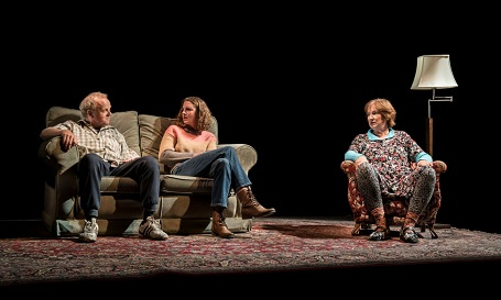 (From Left) Toby Jones, Louisa Harland (the two sitting on a two-person couch facing each other) and Deborah Findlay (on a separate single couch looking at the other two) in Imp at the Royal Court