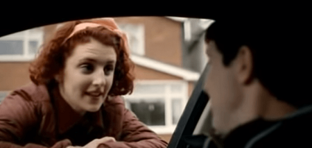 A scene from Love/Hate as Kayleigh peeks into a car window resting her hands on the window with her red hair as the guy in the car is blurry.