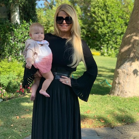 Thin Jessica Simpson in black dress with her left hand on her hip while holding her daughter in her right hand.