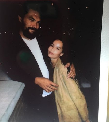 Jason Momoa with his daughter, Zoe Kravitz. The two seem to be in some kind of pub or event.