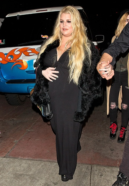 Jessica simpson in a black dress touching her belly during her second pregnancy.
