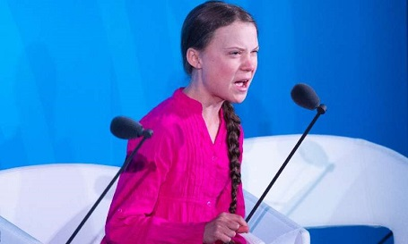 Greta Thunberg sitting in a pink top during a speech at the UN.