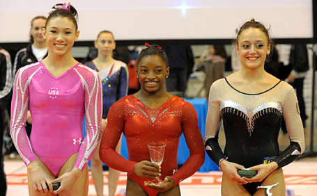 Comparatively short Biles in the middle wearing red gymnastics costume holding a small glass trophy and smiling.