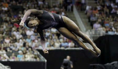 Simone Biles performing a double-twisting, double somersault dismount.