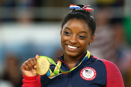 Biles holding a gold medal at the Rio 2016 Olympics.