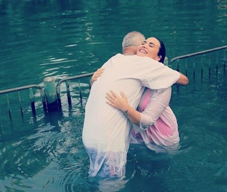 Demi Lovato hugging a baptizer in the holy river in Israel.
