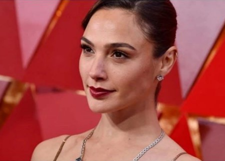 Gal Gadot wearing a diamond earings and a necklace.
