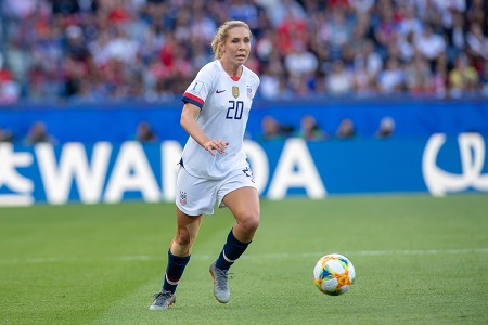 Allie near the ball at the Olympic games against France. Alone in her US Women's soccer uniform.