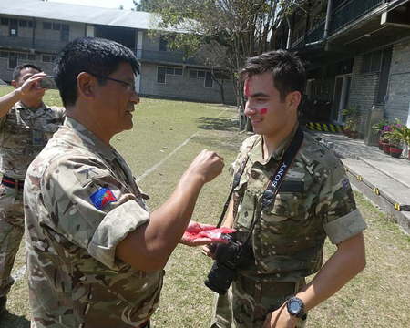 "Senior Gurkha soldier putting on ""tika"" on Benjamin Atkinson's forehead after he completed his 10 week course."