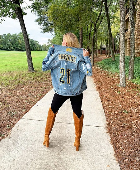 Greinke facing on her back while holding the collar of the Denim jacket she is wearing as described above.