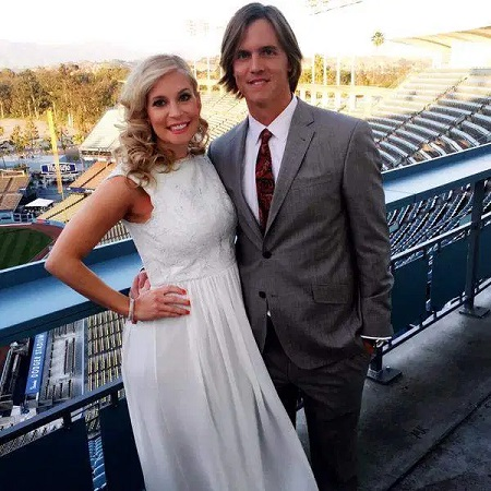Emily (left) in white dress and Zack (right) in a grey suit posing in the stadium stands.