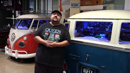 Gabe in front of one of his two Volkswagen buses turned into a fish tank.