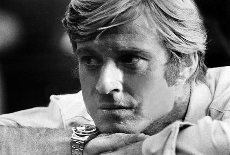 Black & White photo. Robert Redford in his younger years resting his chin in his hands sporting a watch in  his right hand.