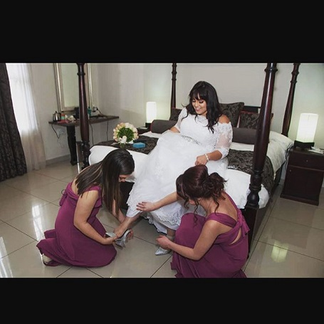 Tiffany smiles as she is sitting on a bed wearing the wedding dress and trying out a shoe her bridesmaid in helping her put on. Another bridesmaid is also there, both wearing brinjal color dresses.
