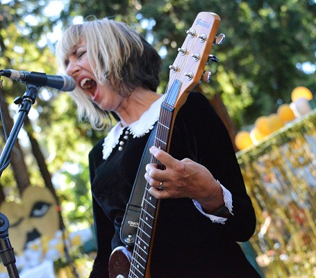 Kim Shattuck in front of a mic singing with a scream playing the guitar in a black dress.