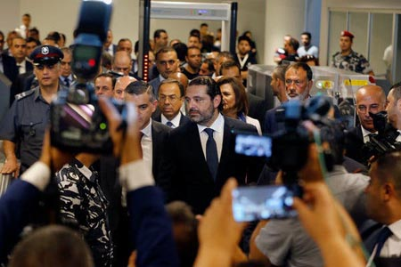 Saad Hariri arrives for a gathering with the press taking photos.