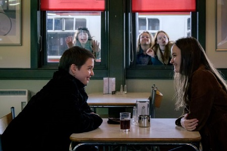 Two of the 'Our Ladies' actresses sitting across a small table in a cafe and smiling as others tease them from the windows.