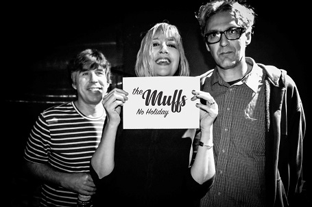 Shattuck holding a card that says 'The Muffs No Holiday' in the middle, with her band members on her sides.