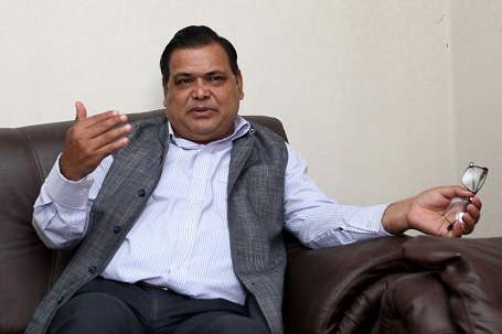 Mahara sitting on a couch, a photo clicked as he is speaking with his right hand raised to his mouth level and spectacle on the other hand, resting on the couch.