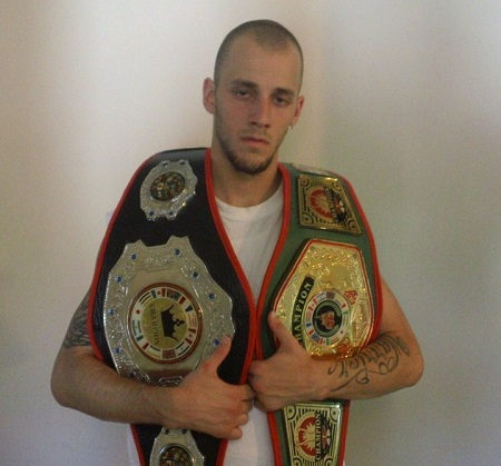 Charlie with two fake boxing belts on his shoulders clutching them.