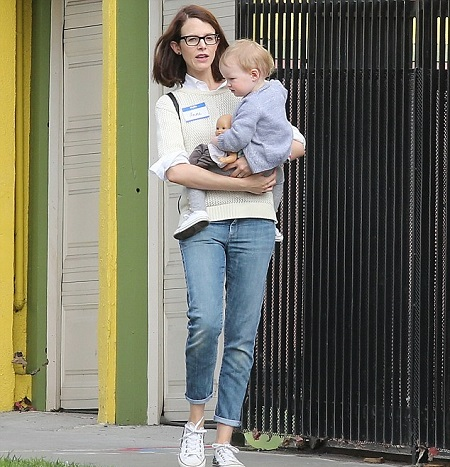 Anne carrying her daughter in her arms as they walk outdoors.
