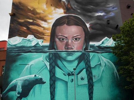 The mural of Greta Thunberg as described above, face partly under glacier water.
