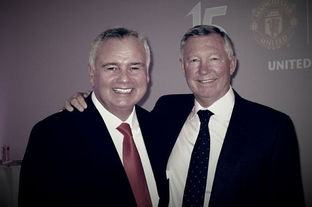 Alex Ferguson with his right hand in Eamonn's right shoulder as they both look at the camera smiling.