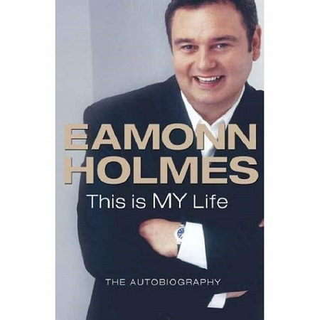 The cover of Eamonn's book 'This is MY Life'. Him folding his arms in a black suit and smiling at the camera.