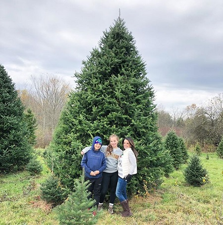 Hollie (right) with her daughter and son in front of a christmas tree before being cut down.