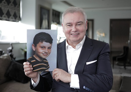 Eamonn holding up a photo of him as a child to his right. Both smiling.
