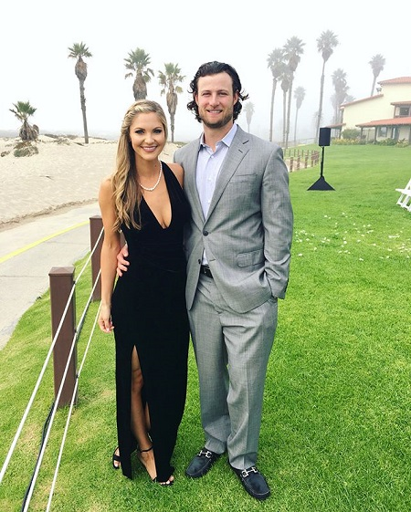 Gerrit Cole with his arm around wife Amy Crawford smiling at the camera. He in a grey suit and she is in a revealing black dress.