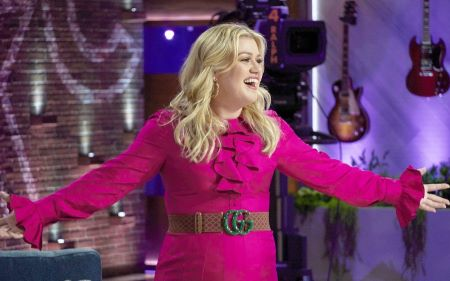 Kelly Clarkson spreading her arms and laughing in a pink dress on her show.