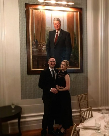 Iliza and Noah at the Yale Club of New York City for a party. A picture of George Bush in the background.