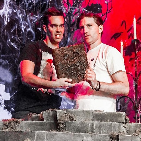 Michael Carbonaro and Peter Stickles holding a horror book and looking horrified.