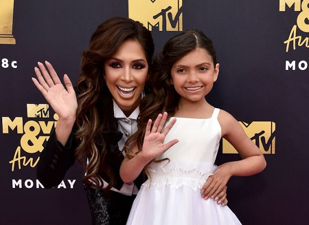 Farrah Abraham with her daughter waving their right hands to the camera at an MTV Movie & Awards show.