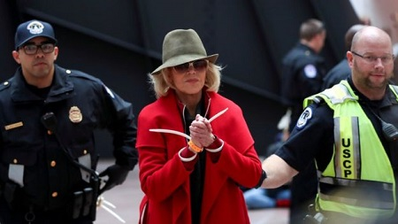 Jane Fonda wearing a red overcoat, a green hat and sunglasses while being arrested with two police authority people with her.