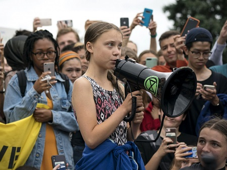 Greta speaking with a boom mic while people surrounding her are taking her pictures and videos on their phones.