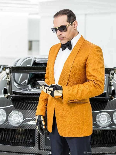 Manny Khoshbin in a yellow suit and glasses looking at a phone in his left hand with driving gloves.