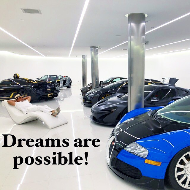 Manny Khoshbin relaxing in a white dress on a white lean-back chair with his $47 million worth car collection featured around him.