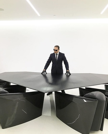 Manny Khoshbin posing in an all black stylish office table like James Bond in an all-white background.