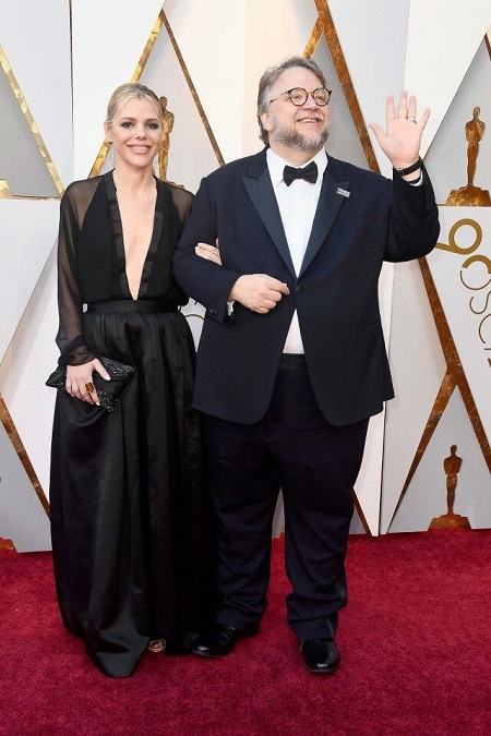 Kim Morgan in black dress (left) arm-in-arm with Guillermo del Toro (right)  waving her arm in the air. Both smiling.