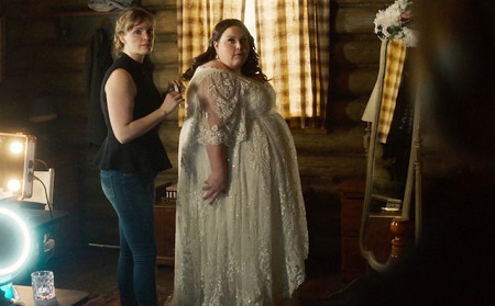 Chrissy (right) in her wedding dress from 'This Is Us' finale facing a mirror facing sideways with a helper behind her also looking sideways.