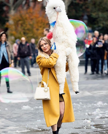 Hilary Duff in a trench coat holding a white stuffed alpaca.