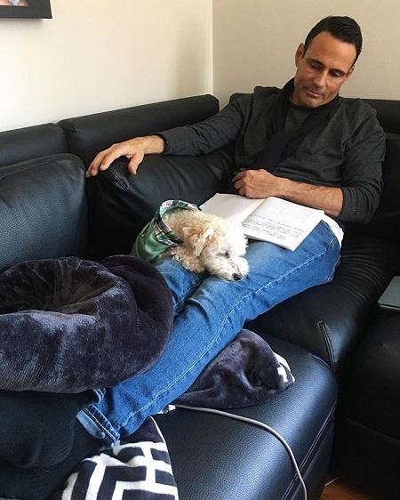 Keven Undergaro in a sofa with his dog resting on his knees.
